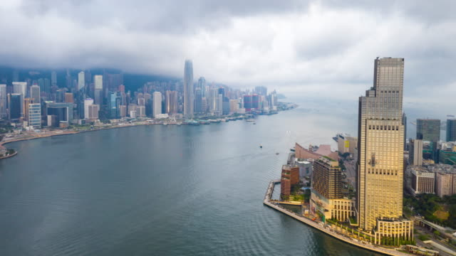 4k hyperlapse : aerial view skyscrapers over victoria harbour  flying by drone of hong kong city with development buildings, transportation, energy power infrastructure.financial and business center asia - victoria peak stock videos & royalty-free footage