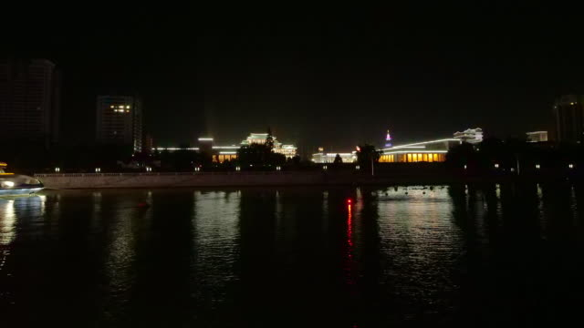 hyper-lapse around grand people's study house at night from a boat-ride on taedong river in pyongyang, north korea, dprk. - spoonfilm stock videos and b-roll footage