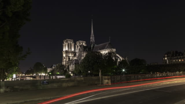 hyperlapse behind notre dame cathedral with car flashing lights on archeveche bridge at night - cristianesimo video stock e b–roll