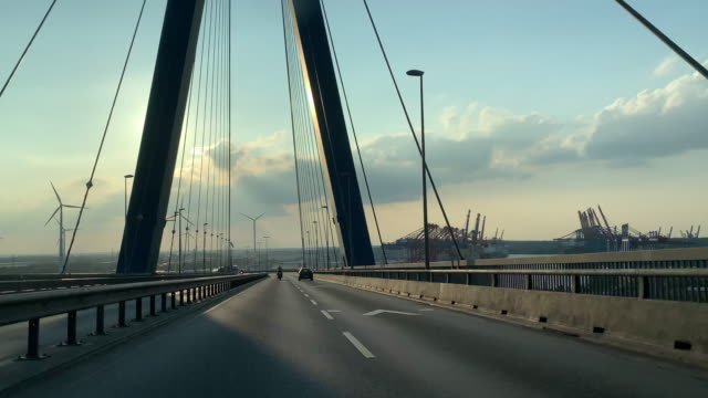 hyperlapse pov driving into the setting sun across the köhlbrand bridge in hamburg, germany - car point of view stock videos & royalty-free footage
