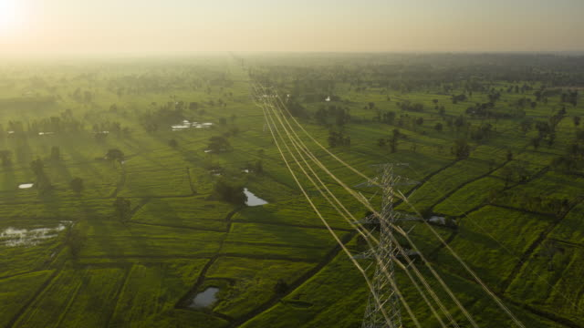 hyperlapse electricity pylons in the sunrise aerial view - elettricità video stock e b–roll