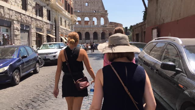 hyperlapse following behind tourists approaching the colosseum, rome - colosseum rome stock videos and b-roll footage