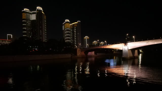 hyper-lapse from a boat-ride on taedong river in pyongyang, north korea, dprk.  passing by illuminated houses under bridge - spoonfilm stock-videos und b-roll-filmmaterial