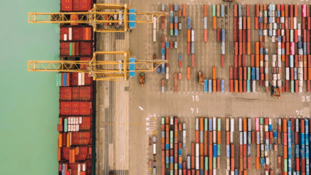 hyperlapse of aerial view of port working cargo container - docks stock videos & royalty-free footage