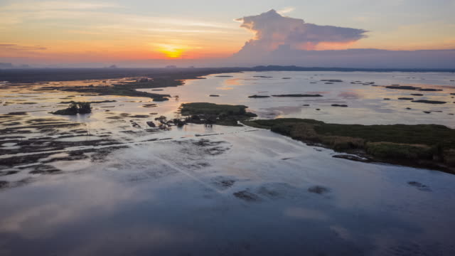 vidéos et rushes de hyperlapse du champ et du lac d'herbe dans la vue aérienne de temps de coucher du soleil - calque