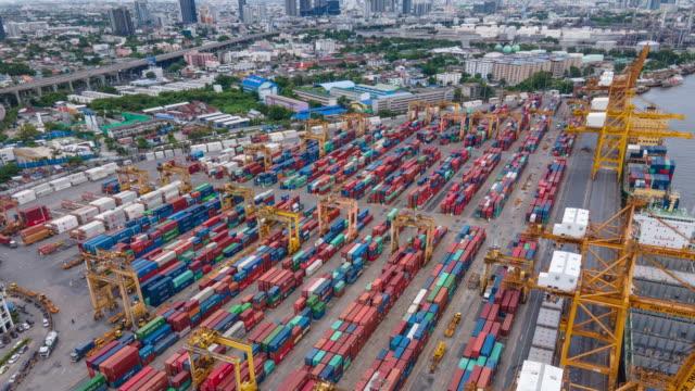 vidéos et rushes de hyperlapse de la logistique et du matériel de transport du navire de cargaison de conteneur et du pont de grue de travail de cargaison dans le chantier naval en asie thaïlande - surchargé de travail