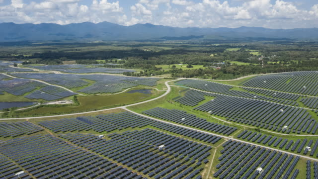 hyperlapse of solar farm with blue sky aerial view - power in nature stock videos & royalty-free footage