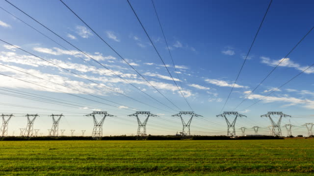 tl hyperlapse on road along electrical towers - power line stock-videos und b-roll-filmmaterial