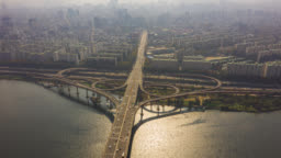 Hyperlapse or Dronelapse Aerial view of Highway road junctions. The Intersecting freeway road overpass of Seoul downtown city skyline with vehicle on expressway and bridge cross over Han river in Seoul city, South Korea.