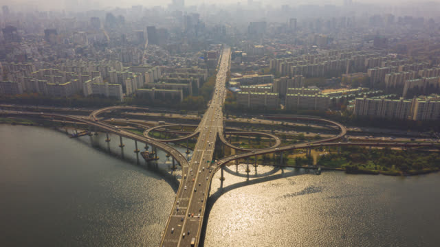 hyperlapse or dronelapse aerial view of highway road junctions. the intersecting freeway road overpass of seoul downtown city skyline with vehicle on expressway and bridge cross over han river in seoul city, south korea. - south korea stock videos & royalty-free footage