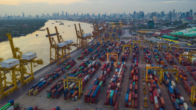vídeos de stock e filmes b-roll de hyperlapse or dronelapse aerial view of international port with crane loading containers in import export business logistics. - docas