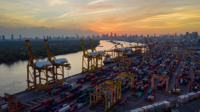 hyperlapse or dronelapse aerial view of international port with crane loading containers in import export business logistics. - chain store stock videos & royalty-free footage