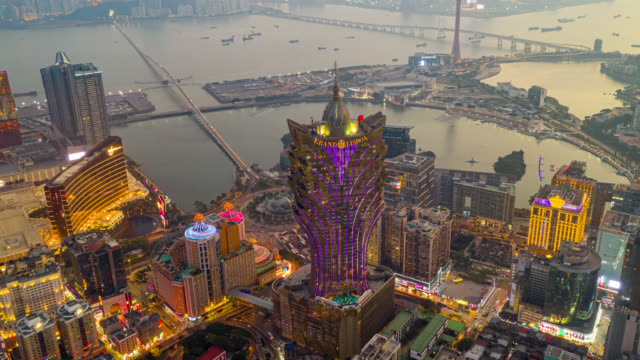 hyperlapse or dronelapse aerial view of macau cityscape and skyscraper in macau city near hong kong island, china at sunset - casino stock videos & royalty-free footage