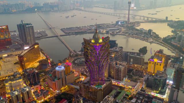 hyperlapse oder dronelapse luftaufnahme von macau cityscape und wolkenkratzer in macau stadt in der nähe von hong kong island bei sonnenuntergang - macao stock-videos und b-roll-filmmaterial