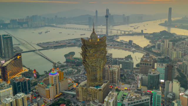 hyperlapse or dronelapse aerial view of macau cityscape and skyscraper in macau city near hong kong island at sunset - macao flag stock videos & royalty-free footage