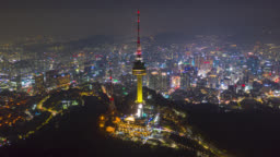 Hyperlapse or Dronelapse Aerial view of N Seoul Tower in Seoul downtown city skyline with light trails on Samson mountain at night in Seoul city, South Korea.