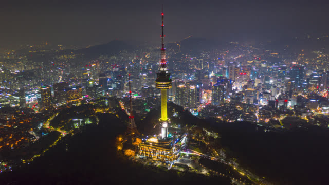 hyperlapse or dronelapse aerial view of n seoul tower in seoul downtown city skyline with light trails on samson mountain at night in seoul city, south korea. - tower stock videos & royalty-free footage