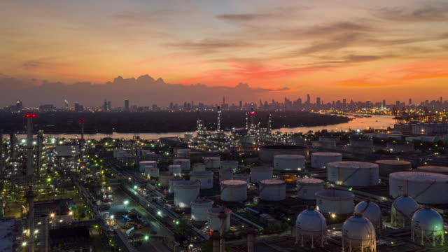 hyperlapse or dronelapse aerial view of oil refinery near international port at sunset. refinery plant at sunset. refinery factory and tank - fossil fuel stock videos & royalty-free footage