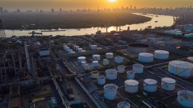 日没時に国際港近くの石油精製所のハイパーラプスまたはドローンラプス空中写真。日没時の製油所工場。製油所工場およびタンク - 貯蔵タンク点の映像素材/bロール