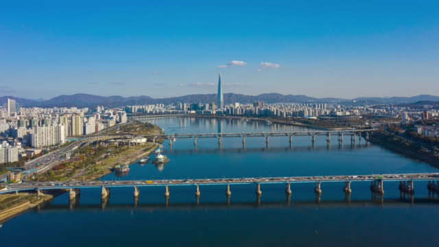 hyperlapse or dronelapse aerial view of seoul downtown city skyline with vehicle on expressway and bridge cross over han river in seoul city, south korea. - seoul stock videos & royalty-free footage