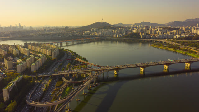 hyperlapse or dronelapse aerial view of seoul downtown city skyline with vehicle on expressway and bridge cross over han river in seoul city, south korea. - river han stock videos & royalty-free footage