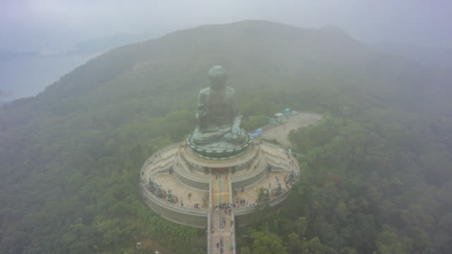 hyperlapse or dronelapse aerial view of tian tan big bhudda statue in foggy and clouldy day, ngong ping 360, hong kong china - god stock videos & royalty-free footage
