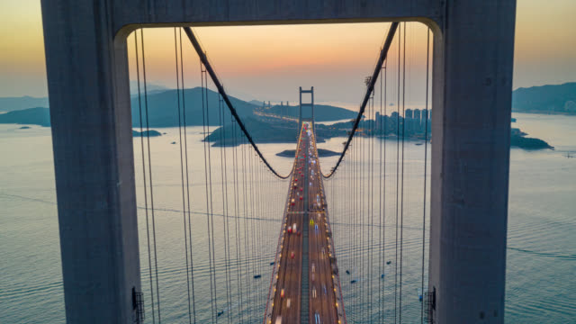 stockvideo's en b-roll-footage met hyperlapse of dronelapse luchtfoto van het verkeer van de auto op tsing ma bridge in tsing yi gebied van hong kong bij zonsondergang. dag tot nacht timelapse - hongkong