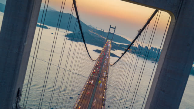 hyperlapse or dronelapse aerial view of traffic of car at tsing ma bridge in tsing yi area of hong kong at sunset. day to night timelapse - hyper lapse stock videos & royalty-free footage