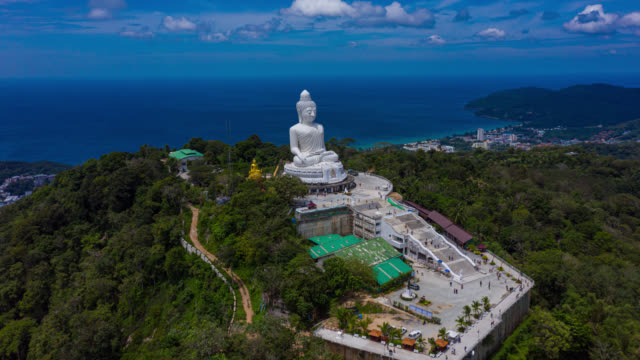 hyperlapse or dronelapse of phuket big buddha on the top of mountain in phuket province at thailand - phuket stock videos & royalty-free footage