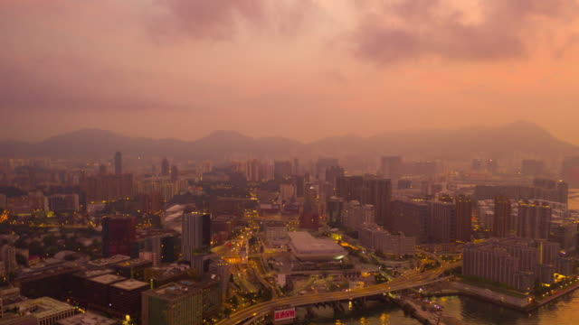 4k hyperlapse : sunrise  building in a city of kowloon island - aerial view skyscrapers flying by drone of hong kong city with development buildings, transportation, energy power infrastructure.financial and business center asia - inquadratura da un aereo video stock e b–roll