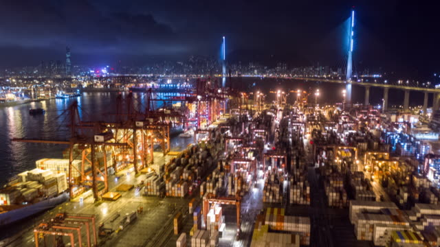 hyperlapse tilt up of commercial container port in night time - stabilimento per il trasporto video stock e b–roll