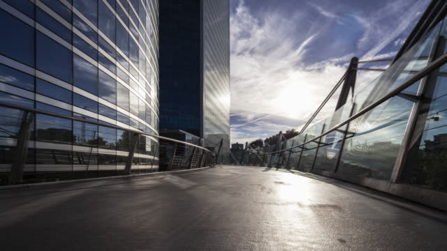 hyperlapse / time lapse at sunset on ramp along office building in business / financial district paris la defense - wide stock videos & royalty-free footage