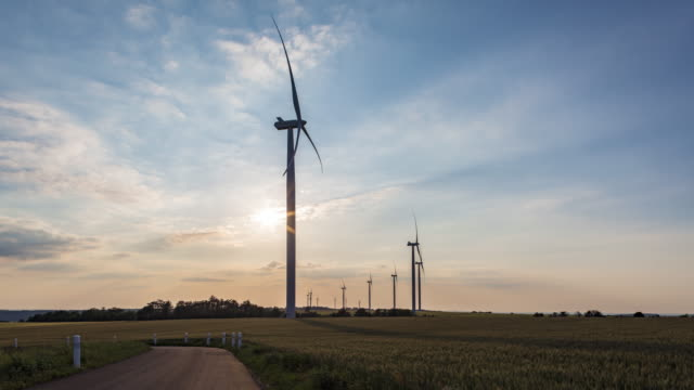 hyperlapse / time lapse of wind farm in sunset - propeller stock videos & royalty-free footage