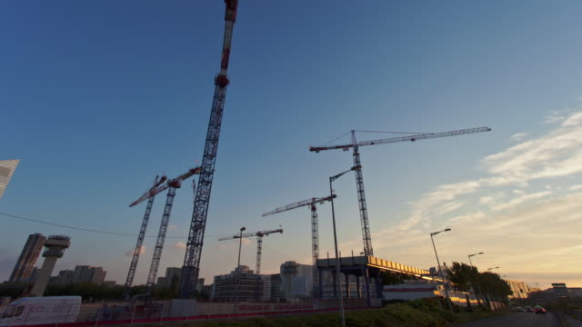 hyperlapse time lapse tracking shot with cranes along building site at sunset in business district  - kran stock-videos und b-roll-filmmaterial