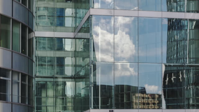 hyperlapse time lapse tracking shot with glass reflections and clouds on office building - Glass Reflection
