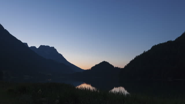Hyperlapse - tracking shot night to day along lake and mountains in Tirol