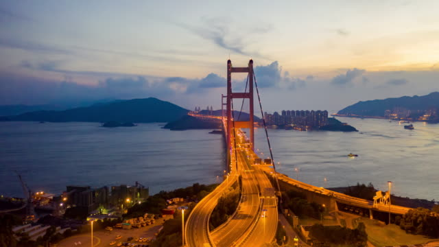 4k hyperlapse : twilight aerial view traffic on bridge  flying by drone of hong kong city with development buildings, transportation, energy power infrastructure.financial and business center asia - inquadratura da un aereo video stock e b–roll