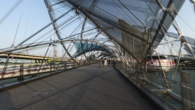 hyperlapse walking through helix bridge to marina bay sand singapore - helix bridge stock videos & royalty-free footage