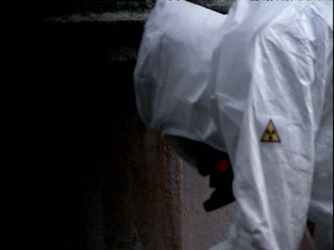 vídeos de stock, filmes e b-roll de hypothetical recreation of aftermath of dirty bomb men wearing white biohazard suits and gas masks scan and scour deserted streets of westminster central london with geiger counters - bomb