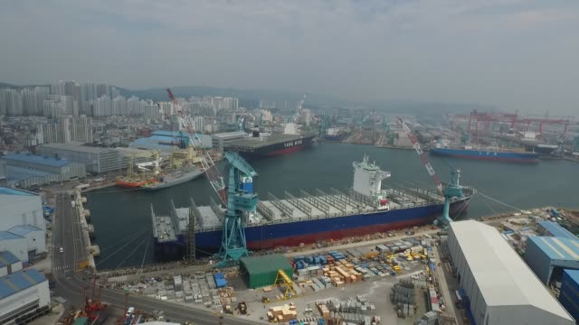 Hyundai Heavy Industries Co excavators and ships under construction in aerial shots taken above the companys plant in Ulsan South Korea on Wednesday...