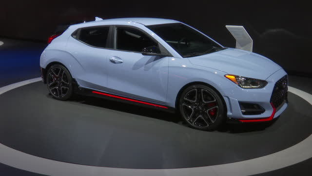 SHOT Hyundai Veloster N revolving on turntable / CLOSEUP headlight ZOOM OUT WS front end / MEDIUM SHOT front seats / WS HIGH ANGLE looking down on...