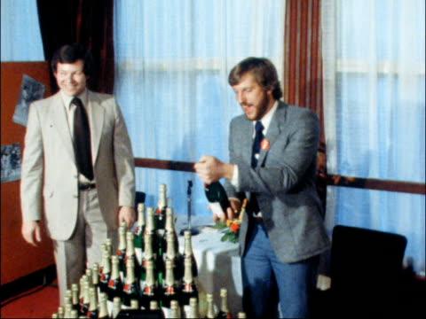 Ian Botham given 100 bottles of champagne ITN London Botham and pyramid of champagne bottles opens one PAN RL sprays press PAN MS Press MS Botham and...