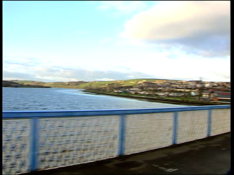 i/c as into car view as travelling over craigavon bridge pan tms cars crossing bridge pan into the bogside mural showing police and soldier beating... - ロンドンデリー点の映像素材/bロール
