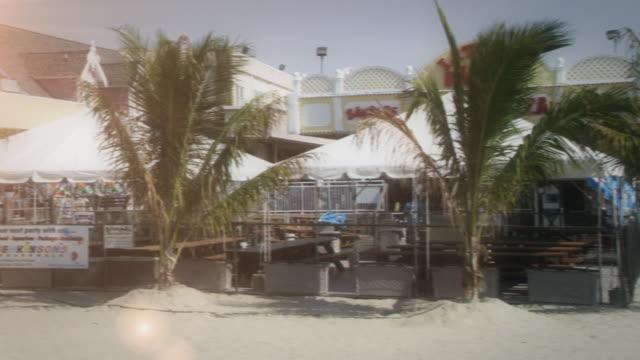 vídeos de stock e filmes b-roll de ice and snow freezes a tropical beach and cabanas. - desvanecido efeito de imagem