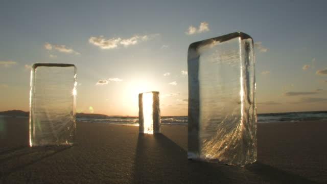 stockvideo's en b-roll-footage met ice blocks on beach at sunset - kleine groep dingen