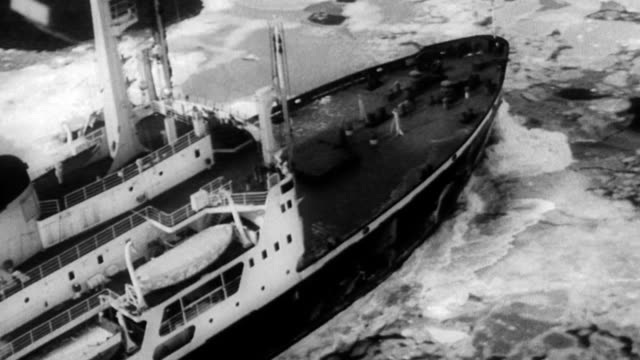 Ice breaker ship moving slowly through icy waters / CU of ice breaking on ocean / aerial of ship moving in water / dolphins play in ocean waves /...