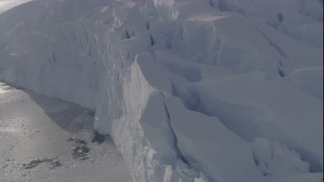 ice chunks float in a sea below a crumbling glacier in antarctica. available in hd - bbc stock videos and b-roll footage