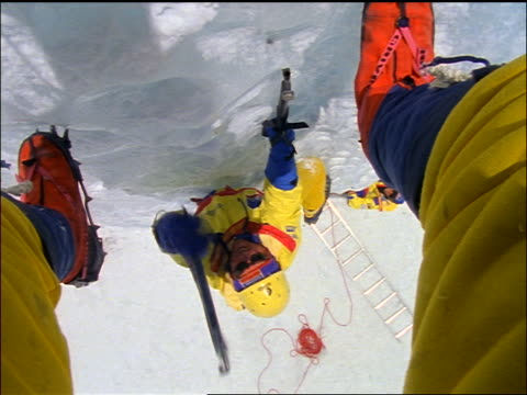 ice climber overhead point of view between legs of male climber using ice picks / everest expedition - mount everest stock-videos und b-roll-filmmaterial