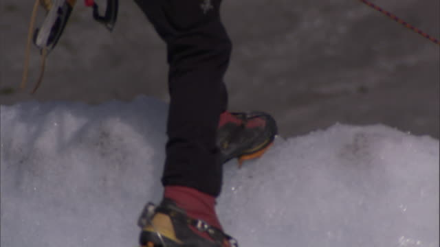 ice climbers use crampons and ropes to descend an ice wall. - safety harness stock videos & royalty-free footage