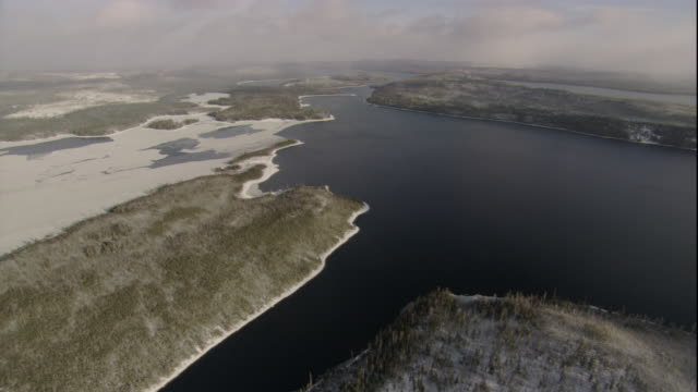 ice covers part of an inlet in a snowy taiga forest area. available in hd. - inlet stock videos & royalty-free footage